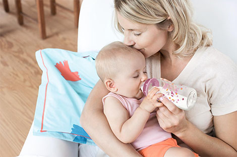 El bebé recibe el biberón de su madre