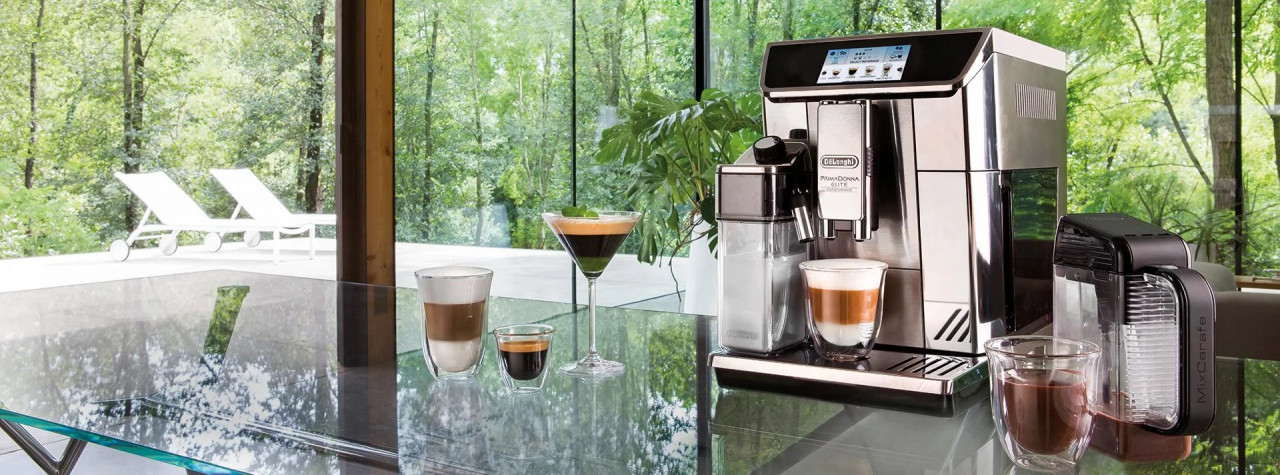 De'Longhi Emotions picture with coffee drinks on glass table and forest in the background